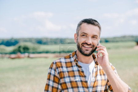 smiling middle aged farmer talking by smartphone in field