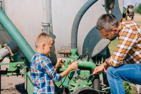 Photo for Father and son repairing agricultural vehicle together - Royalty Free Image