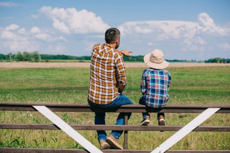 Photo for Back view of father and son sitting on fence and looking at green  field - Royalty Free Image