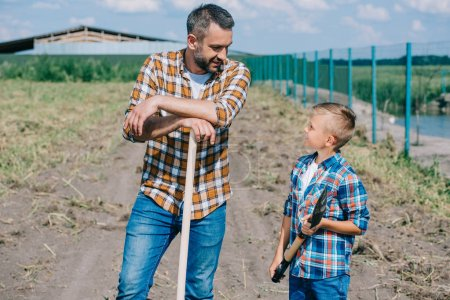 father and son holding shovels and looking at each other on farm