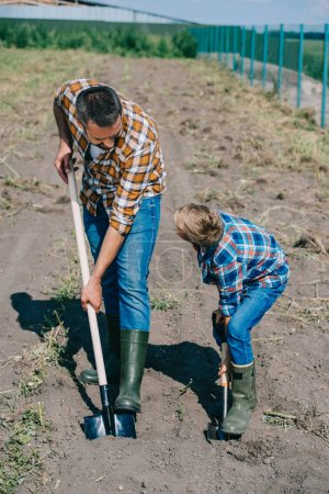 high angle view of father and son looking at each other while working with shovels in field