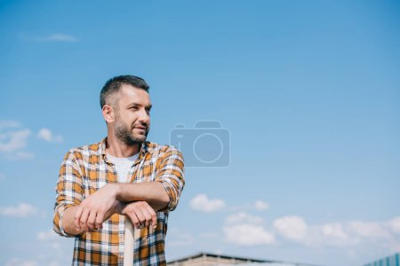 handsome farmer in checkered shirt leaning on shovel and looking away