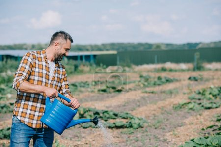 handsome farmer in checkered shirt holding watering can and working in field