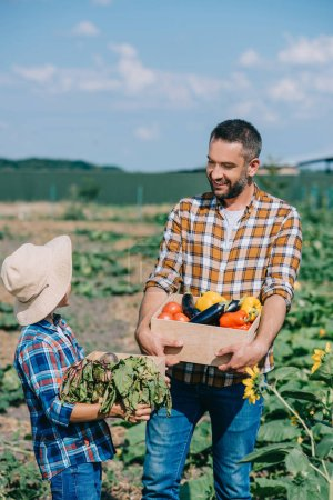happy father and son holding boxes with ripe vegetables and smiling each other in field