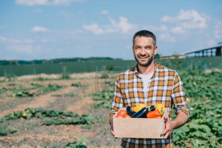 happy handsome farmer holding box with fresh ripe vegetables and smiling at camera