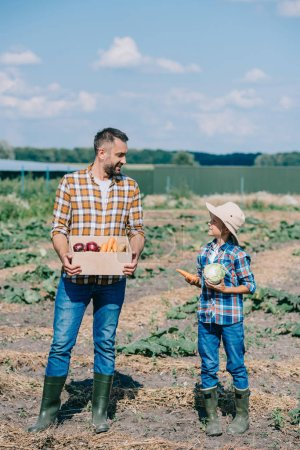Photo for Happy father and son holding ripe vegetables and smiling each other in field - Royalty Free Image