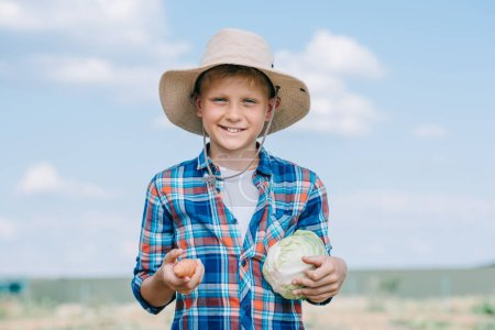happy boy in panama hat holding ripe vegetables and smiling at camera outdoors