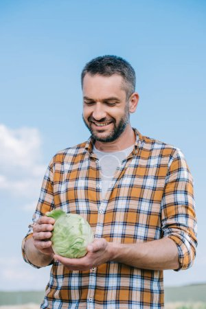 happy handsome farmer holding fresh cabbage outdoors