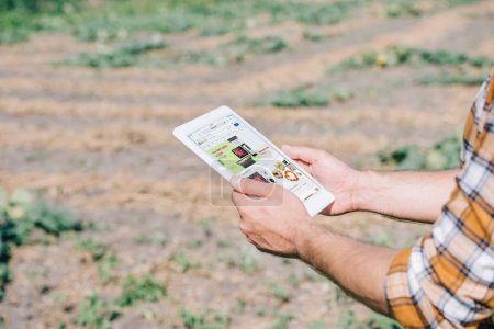 Photo for Cropped shot of farmer using digital tablet with ebay website while standing on field - Royalty Free Image