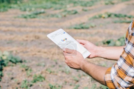 cropped shot of farmer using digital tablet with google website while standing on field