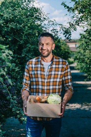 happy farmer holding box with fresh vegetables and smiling at camera