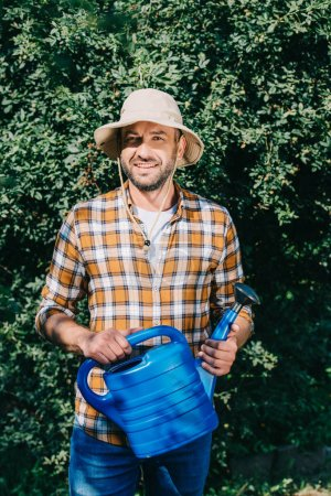 handsome male farmer in checkered shirt holding watering can and smiling at camera outdoors