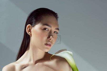 beautiful naked tender asian girl with calla flower, isolated on grey