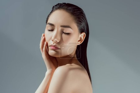 beautiful tender asian girl with closed eyes, isolated on grey
