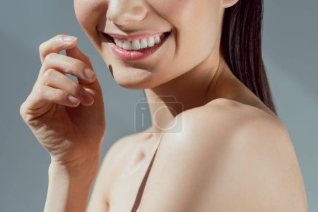cropped view of beautiful smiling girl, isolated on grey