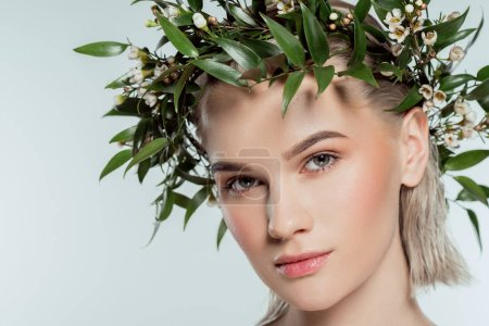 beautiful blonde girl in green floral wreath, isolated on grey