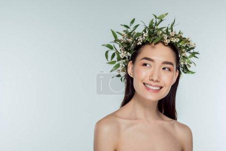 attraktive nackte asiatische Mädchen in grünem Blumenkranz, isoliert auf grau