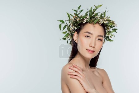 attractive naked asian girl in floral wreath, isolated on grey