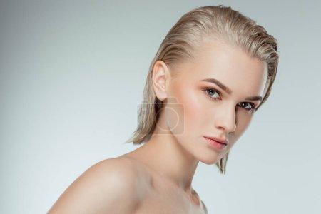 Portrait de jolie jeune fille blonde, isolée sur fond gris