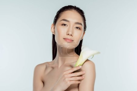 beautiful nude asian girl posing with calla flower, isolated on grey