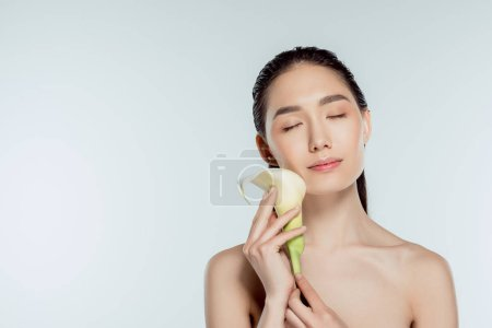 Photo for Beautiful asian girl with closed eyes holding calla flower, isolated on grey, natural beauty - Royalty Free Image