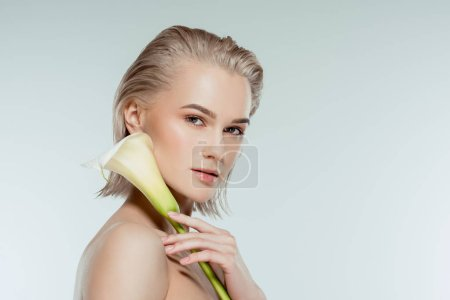 beautiful nude blonde girl posing with calla flower, isolated on grey