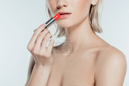 beautiful woman applying red lipstick, isolated on grey