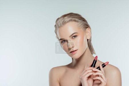 beautiful woman holding lipsticks, isolated on grey