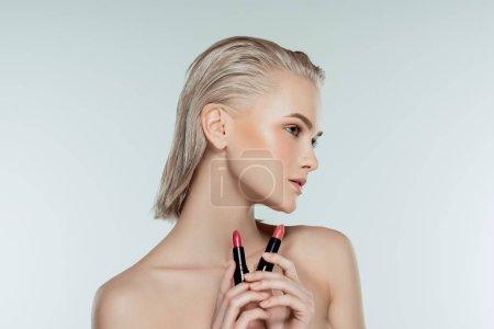 beautiful blonde woman holding lipsticks, isolated on grey