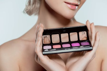cropped view of girl holding palette with eyeshadows, isolated on grey