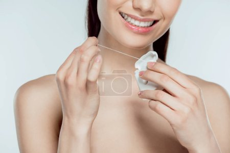 cropped view of smiling woman holding dental floss, isolated on grey