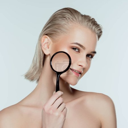 beautiful girl with magnifier, skin care concept, isolated on grey