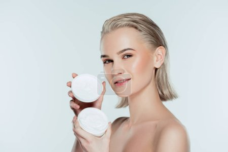 nude woman holding face cream in plastic container, isolated on grey