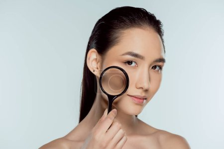 beautiful asian girl with pure skin holding magnifier, skin care concept, isolated on grey
