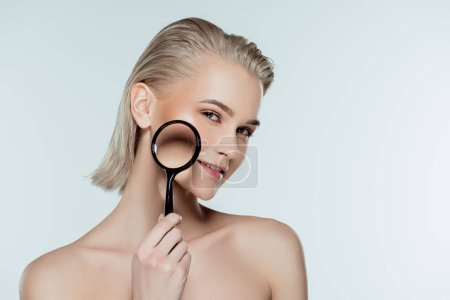 attractive girl with pure face holding magnifying glass, skin care concept, isolated on grey