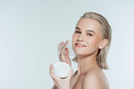 happly woman applying face cream, isolated on grey
