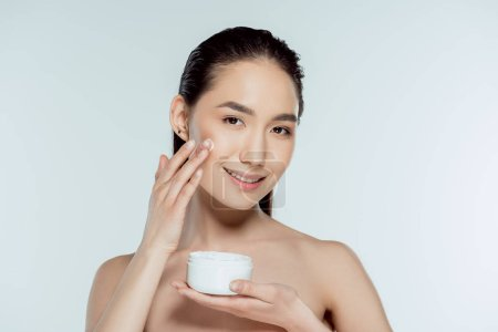 attractive asian woman applying face cream, isolated on grey