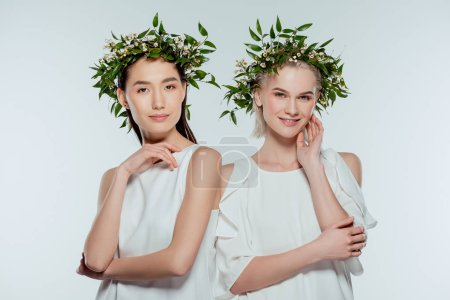 asian and caucasian girls posing in green floral wreaths, isolated on grey