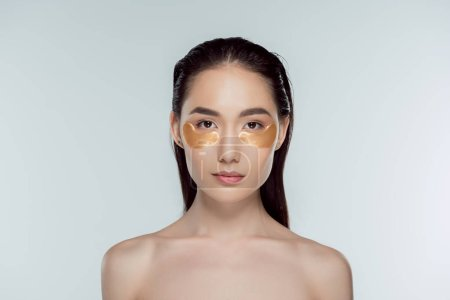 beautiful asian girl with golden eye patches, isolated on grey