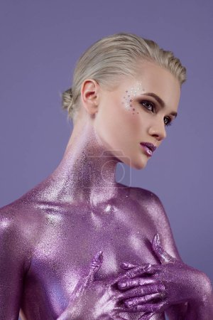 attractive girl painted with ultra violet glitter, isolated on purple