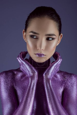 stylish attractive asian girl in ultra violet glitter, isolated on purple