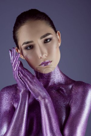 tender asian girl posing in ultra violet glitter, isolated on purple