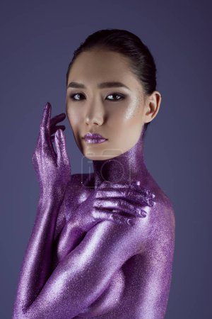 tender fashionable asian girl in ultra violet glitter, isolated on purple
