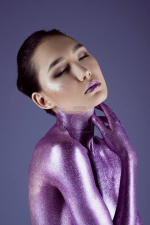fashionable sensual asian girl in ultra violet glitter, isolated on purple