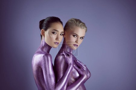 Photo for Multicultural naked women in purple glitter hugging each other, isolated on violet - Royalty Free Image