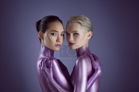 Photo for Beautiful multicultural girls in ultra violet glitter hugging each other, isolated on purple - Royalty Free Image