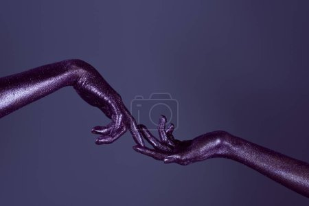 cropped view of girls hands in glitter touching each other with fingers, isolated on purple