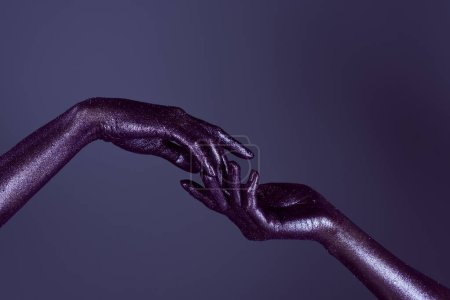 partial view of womens hands in ultra violet glitter touching each other, isolated on purple
