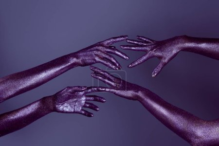 cropped view of girls hands in glitter touching each other, isolated on purple