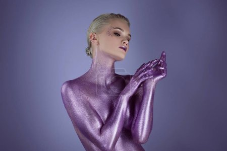 tender stylish girl painted with ultra violet glitter, isolated on purple